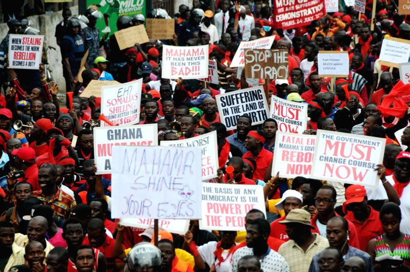 People demonstrate with slogans in their hands on the streets of Accra, the capital of Ghana, July 24, 2014. Thousands of people were on a one-day demonstration in ...
