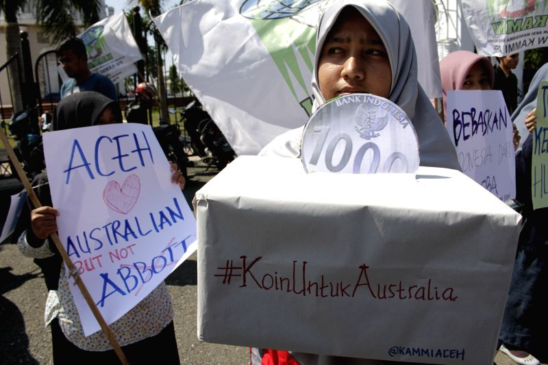An Indonesian Muslim student puts a symbolic coin into a savings box during a protest against Australian Prime Minister Tony Abbot's statement in Aceh, Indonesia, Feb. ... - Tony Abbo
