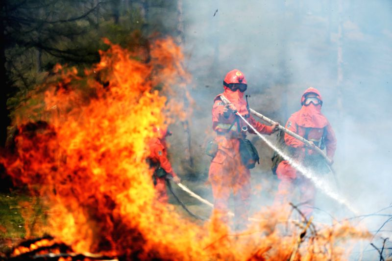 Firemen put out a fire during a drill in Acheng, northeast China's Heilongjiang Province, April 24, 2014. The forest firemen detachment of Harbin City carried out a
