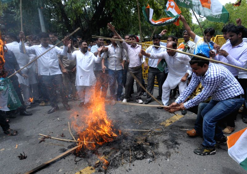 Activists from Indian opposition Congress Party burns an effigy of Prime Minister Narendra Modi as they shout anti-government slogans during a protest against the hike in rail fares in front of ...
