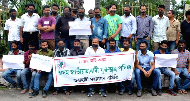 Activists of Asom Jatiyatabadi Yuba Chatra Parishad (AJYCP) tie black cloths in their mouths sit in protest against central goverment decision in raising Railway fare in Guwahati on June 21, 2014.