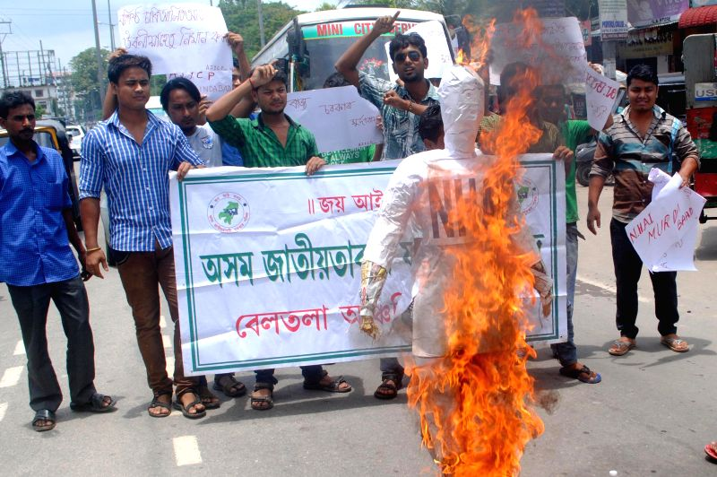 Activists of Asom Jatiyatabadi Yuba-Chatra Parishad, burns the effigy of National Highway Authority of India, in demands of a fly over bridge at Basista Chariali, in Guwahati on June 28. 2014.