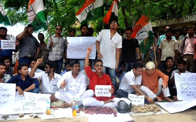 Activists of Asom Yuva Santha (AYS) burn effigies of Prime Minister Narendra Modi and Assam Chief Minister Tarun Gogoi against hike in prices of Petrol, Diesel and electricity in Guwahati on July 1, . - Narendra Modi