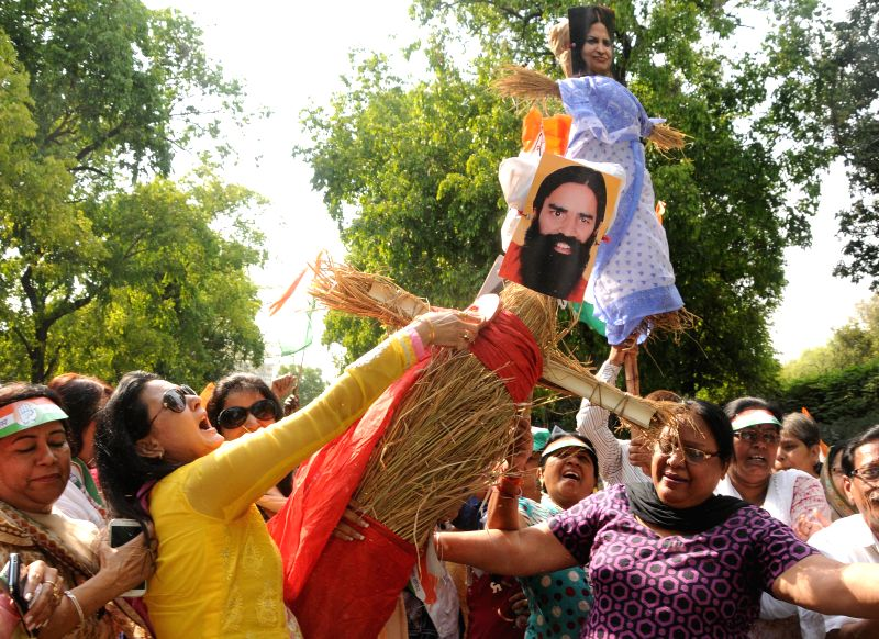 Activists of Delhi Mahila Congress burn an effigy of Yoga guru Ramdev during a demonstration in New Delhi on May 1, 2014.