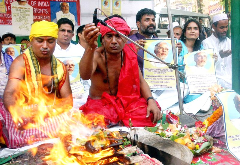Activists of Human Right Protection Association burn posters of BJP Prime Ministerial candidate and Gujarat Chief Minister Narendra Modi during a 'hawan' in Kolkata on April 11, 2014. - Narendra Modi