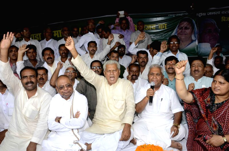 Activists of RJD sit in protest against central goverment decision in raising Railway fare in Patna on June 21, 2014.