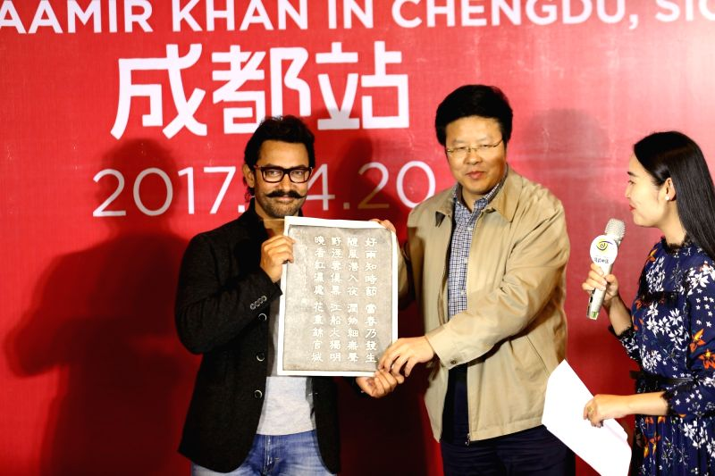 Actor Aamir Khan receives a rubbed copy of a poem by ancient Chinese poet Du Fu during a press conference at the Thatched Cottage of Du Fu in Chengdu city in southwest China's Sichuan ... - Aamir Khan