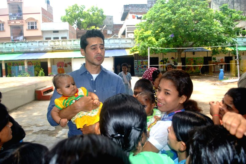 Actor Dino Morea interacts with inmates during his visits to a Women's Correctional Home in Varanasi on May 7, 2016. - Dino Morea