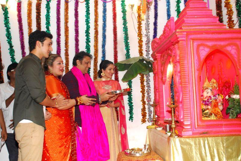 Actor Govinda with his wife Sunita and son Yashowardan daughter Narmada during the Ganesh Chaturthi celebrations at his residence in Mumbai on Aug 29, 2014.
