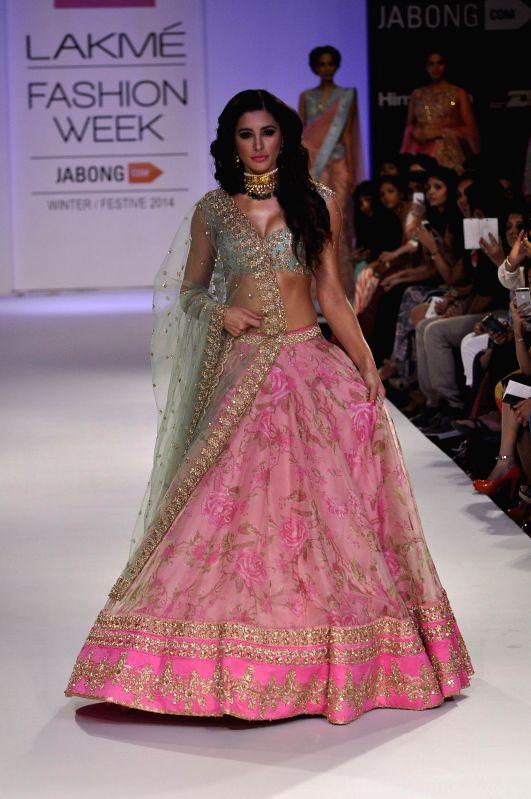 Actor Nargis Fakhri displays the creation of fashion designer Anushree Reedy during the Lakme Fashion Week (LFW) Winter/ Festive 2014 in Mumbai, on Aug. 23, 2014. - Nargis Fakhri