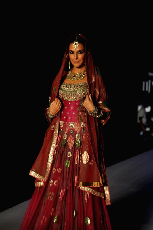 Actor Neha Dhupia walks on the ramp displays Jewellery design by Queenie Singh during the India International Jewellery Week (IIJW) in Mumbai, on July 14, 2014. - Queenie Singh