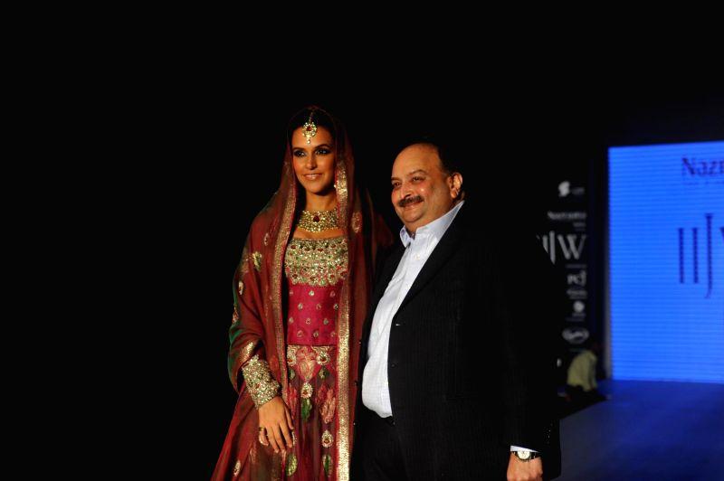 Actor Neha Dhupia walks on the ramp displays Jewellery design by Queenie Singh during the India International Jewellery Week (IIJW) in Mumbai, on July 14, 2014. - Queenie Singh