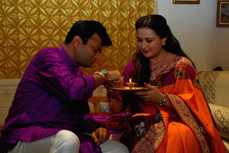 Actor Poonam Dhillon with her brother Aneel Murarka celebrates the Raksha Bandhan festival in Mumbai on August 5, 2014.