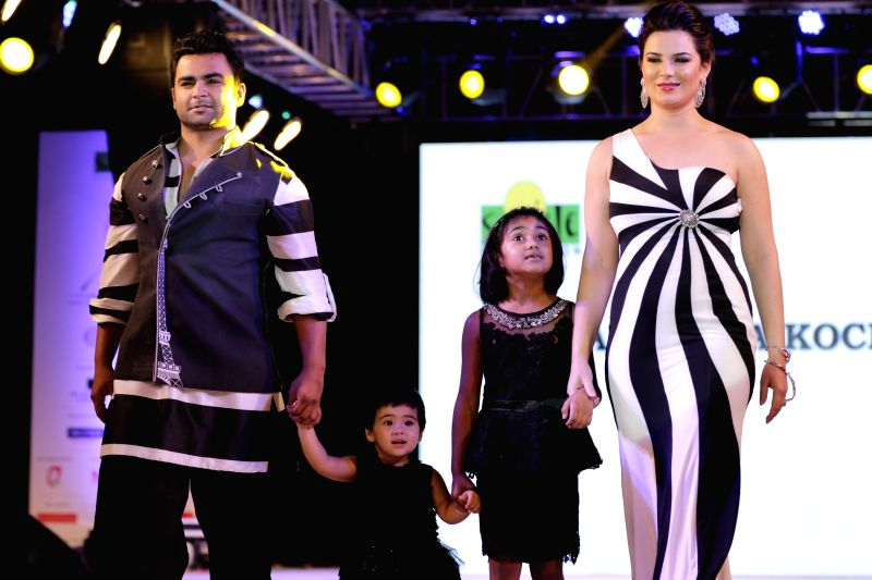 Actor Sachiin Joshi along with wife and actor Urvashi Sharma walks the ramp during for 9th edition of charity fashion show organized by Smile Foundation in Mumbai, on August 2, 2015. - Sachiin Joshi and Urvashi Sharma