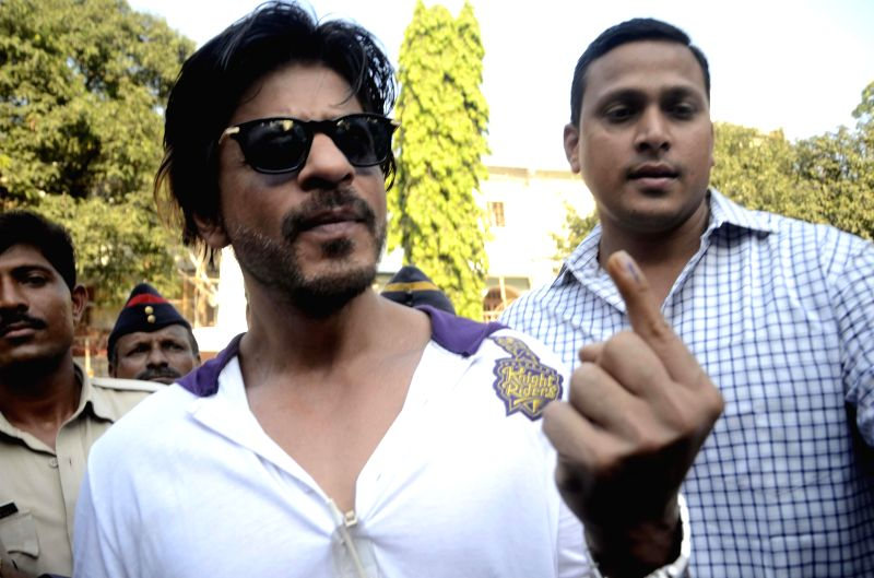 Actor Shahrukh Khan shows his fore finger marked with phosphorous ink after casting his vote at a polling booth during the sixth phase of 2014 Lok Sabha Polls  in Mumbai on April 24, 2014.