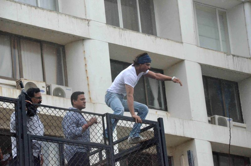 Actor Shahrukh Khan waves as he greets fans gathered outside his residence during the Muslim festival of Eid ul-Fitr in Mumbai on July 29, 2014.
