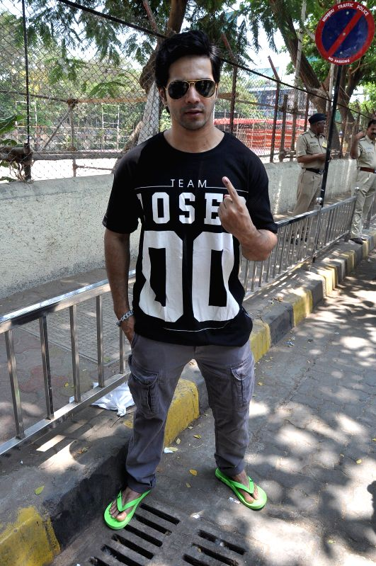 Actor Varun Dhawan shows his fore finger marked with phosphorous ink after casting his vote at a polling booth during the sixth phase of 2014 Lok Sabha Polls in Mumbai on April 24, 2014. - Varun Dhawan