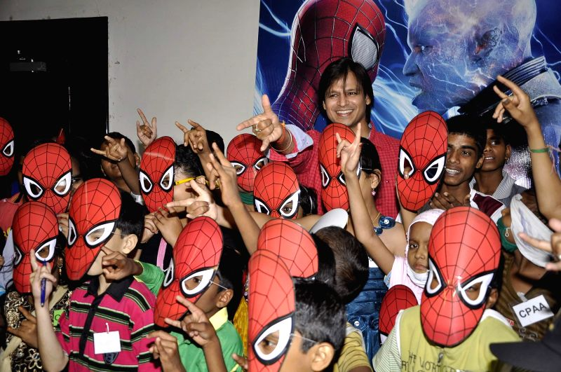 Actor Vivek Oberoi with cancer affected kids during a special screening of Hollywood film The Amazing Spiderman 2 in Mumbai on May 12, 2014. - Vivek Oberoi