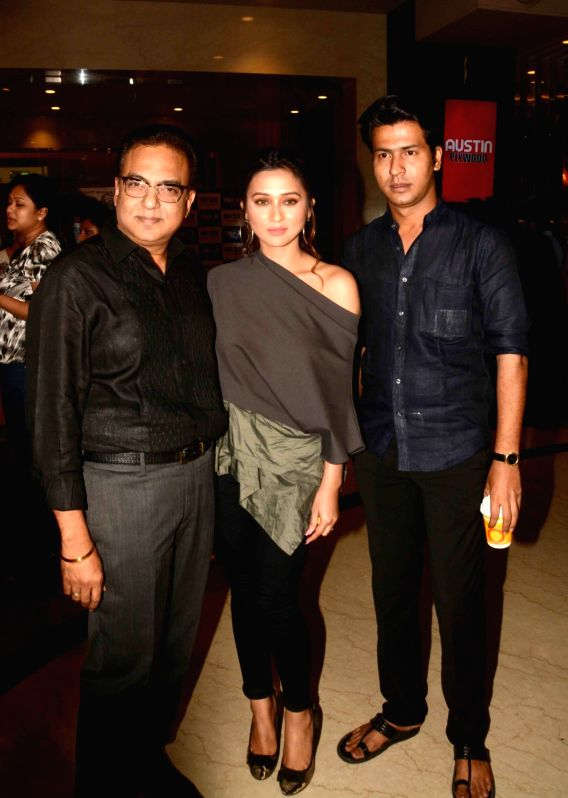 "Actors Anirban Bhattacharya, Mimi Chakraborty with Director Arindam Sil during the premiere of the film ""Dhananjoy"" in Kolkata on Aug 11, 2017. - Anirban Bhattacharya and Mimi Chakraborty"