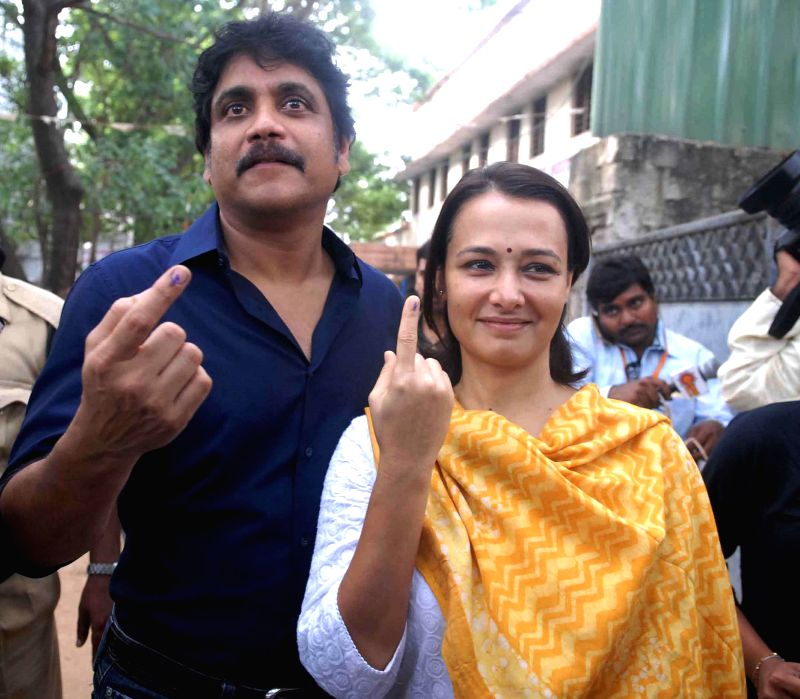 Actors Nagarjuna and Amala show their fore fingers marked with phosphorous ink after casting their votes at a polling booth in Hyderabad on April 30, 2014.
