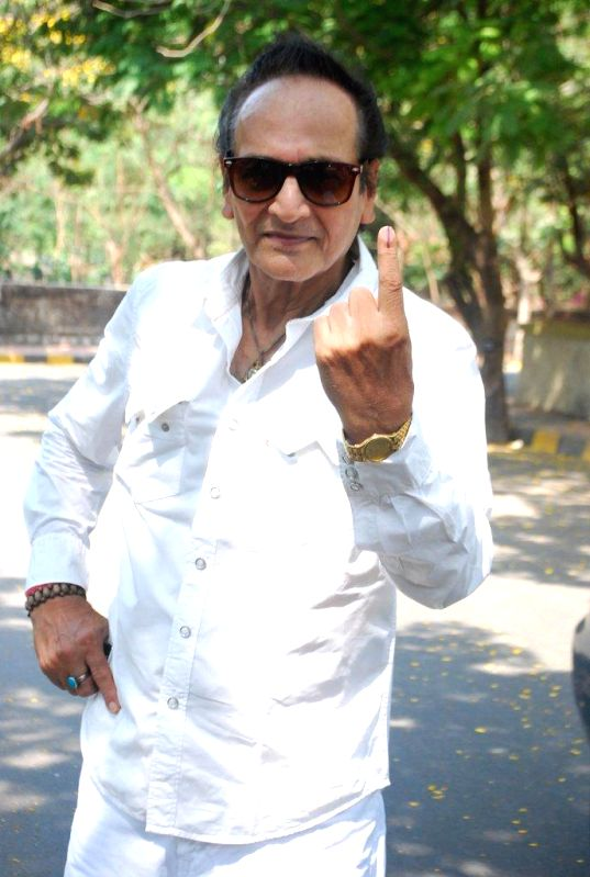 Actress Biswajit Chatterjee shows his fore finger marked with phosphorous ink after casting his vote at a polling booth during the sixth phase of 2014 Lok Sabha Polls in Mumbai on April 24, 2014.