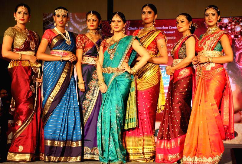 Actress Harshika Poonacha (C) with models during a jewelry show, in Bengaluru on June 12, 2018. - Harshika Poonacha
