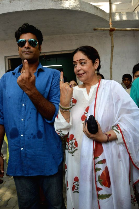 Actress Kirron Kher with son Sikandar Kher shows their fore fingers marked with phosphorous ink after casting his vote at a polling booth during the sixth phase of 2014 Lok Sabha Polls in Mumbai on .. - Kirron Kher and Sikandar Kher