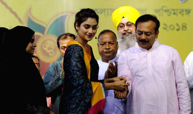 Actress Noor Jahan ties a `rakhi` on the wrist of West Bengal Housing and Youth Affairs Minister Aroop Biswas during `Raksha Bandhan Utsab` in Kolkata on Aug 10, 2014. - Noor Jahan