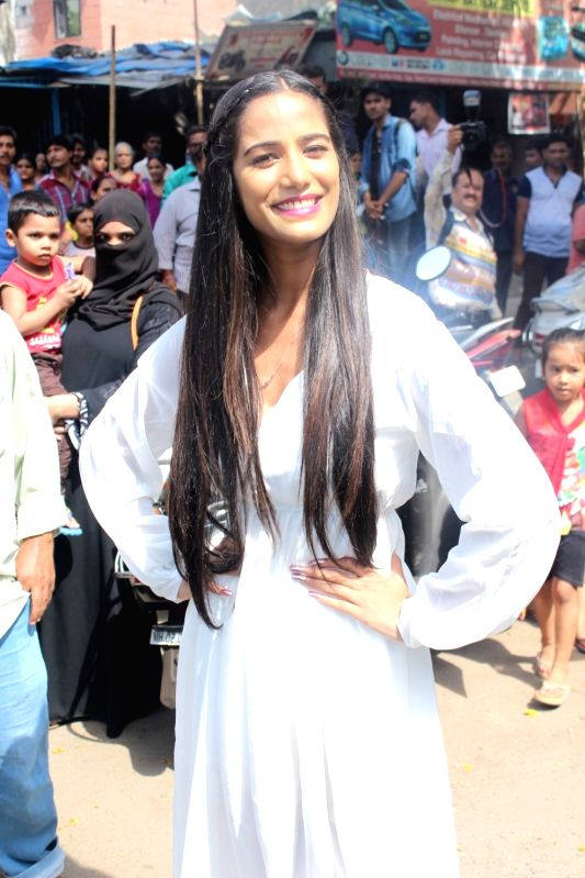 Actress Poonam Pandey poses for the photographers after distributing raincoats to street children in Mumbai, on May 30, 2017. - Poonam Pandey