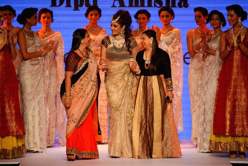 Actress Raveena Tandon walks the ramp displaying jewellery designed by Dipti (L) & Amisha (R) during the India International Jewellery Week (IIJW) in Mumbai, on July 15, 2014.