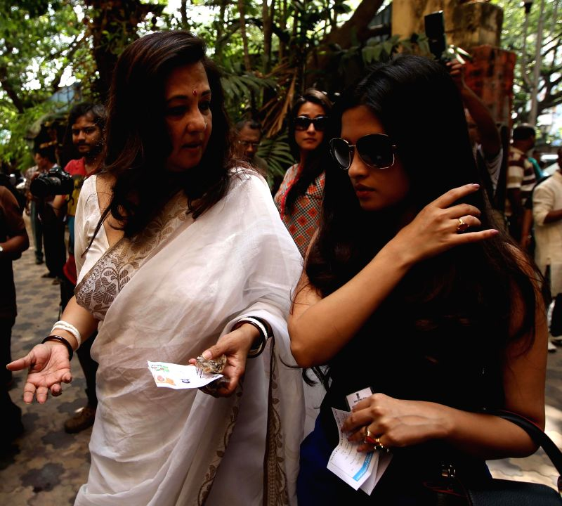 Actress Riya Sen and her mother, Trinamool Congress candidate for 2014 Lok Sabha Election from Bankura, Moon Moon Sen arrive at a polling booth to cast their votes during the ninth phase of 2014 Lok . - Riya Sen