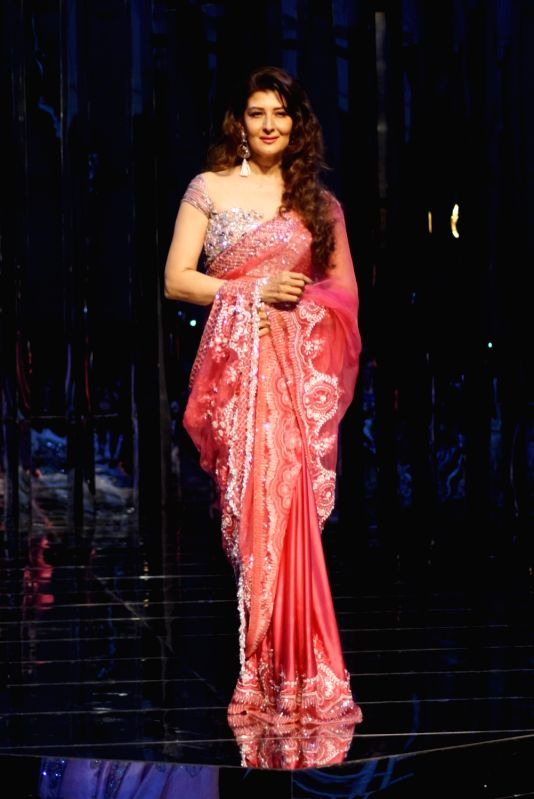 Actress Sangeeta Bijlani walks the ramp for fashion designer Manish Malhotra's haute couture show, in Mumbai on Aug 1, 2018. - Sangeeta Bijlani and Manish Malhotra