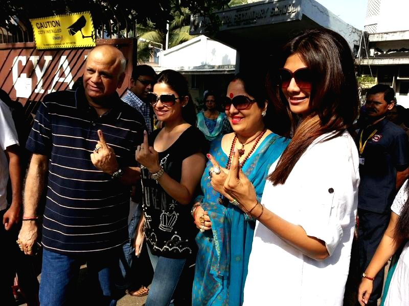 Actress Shilpa Shetty and her family members show their forefingers marked with phosphorous ink after casting their votes at a polling booth during the sixth phase of 2014 Lok Sabha Polls in Mumbai ..