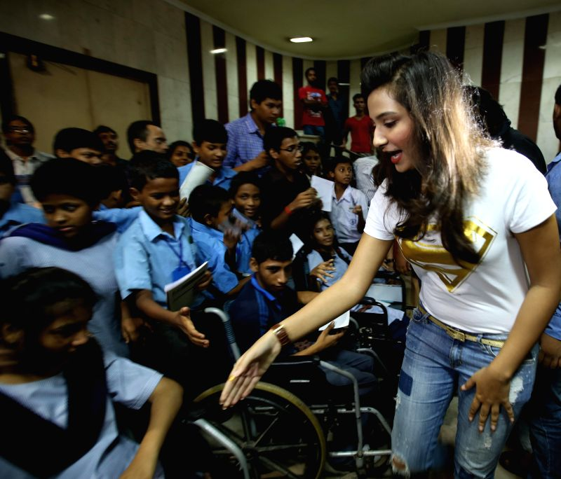 Actress Subhasree Ganguly with children of Indian Institute of Cerebral Palsy during special screening of Bengali film 'GAME' at Bijoli Theatre in Kolkata on June 27, 2014. - Subhasree Ganguly