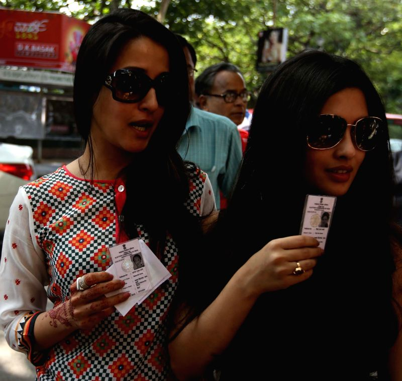 Actresses Raima Sen and Riya Sen arrive at a polling booth to cast their votes during the ninth phase of 2014 Lok Sabha Polls in Kolkata on May 12, 2014. - Raima Sen and Riya Sen
