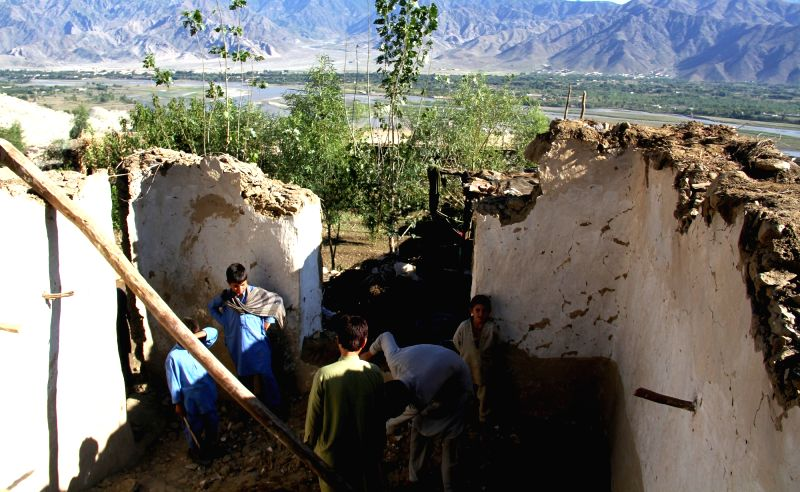 Afghan men clean the debris of a destroyed house in Sawki district of eastern Kunar province, Afghanistan, Oct. 28, 2015. The death toll in Afghanistan of Monday's ...
