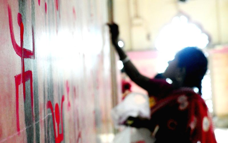 A lady draws a `swastik` symbols on the walls of a temple on `Poila Baisakh` - Bengali New Year, 1422 - in Agartala on April 15, 2015.