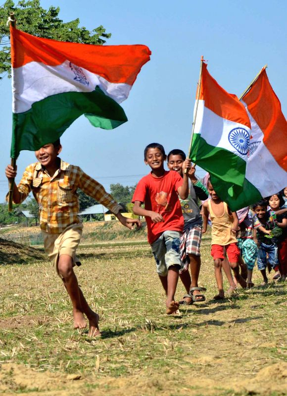 Children run waving Indian flag on the eve of Republic Day in Agartala, on Jan 25, 2015.