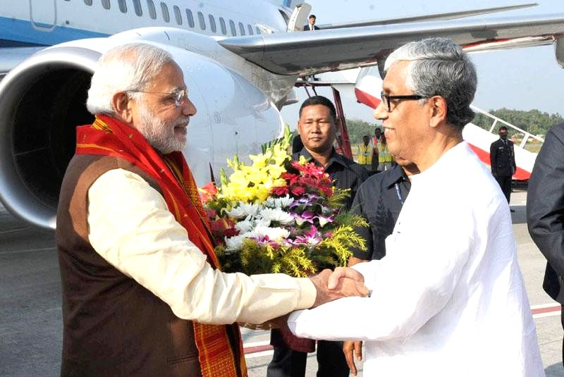 Prime Minister Narendra Modi being received by Tripura Chief Minister on his arrival in Agartala, Tripura on Dec 1, 2014. - Narendra Modi