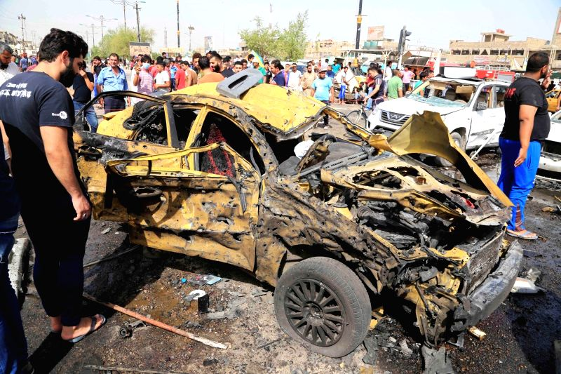 AGHDAD, May 17, 2016 - A man inspects a destroyed car at the expolsion site after an attack killing around 16 people and wounding 53 others in Sadr City in eastern Baghdad, Iraq, on May 17, 2016.