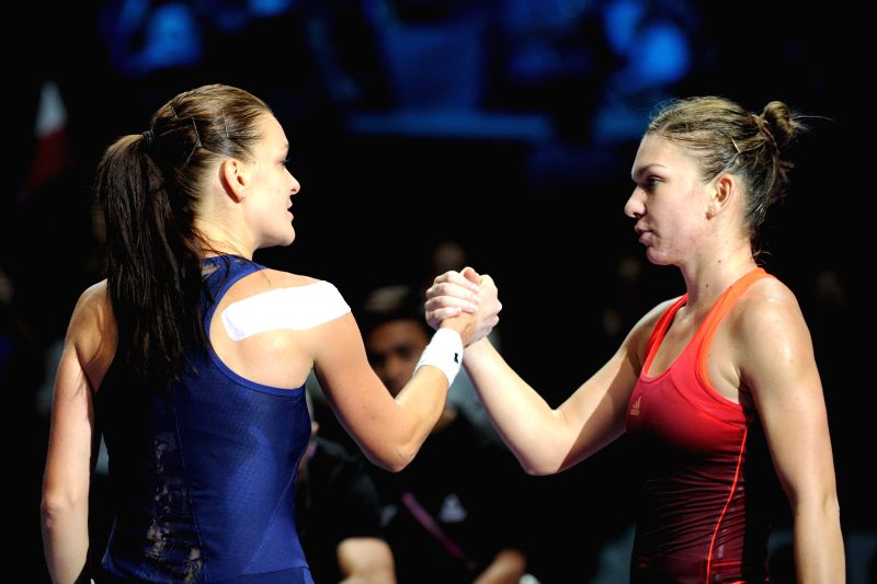 Agnieszka Radwanska of Poland (L)shakes hands with Simona Halep of Romania after their WTA Finals match in Singapore, Oct. 29, 2015. Radwanska won 2-0. ...