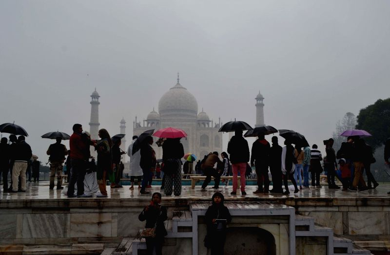 People visit the Taj Mahal on a rainy day in Agra, on Jan 22, 2015.