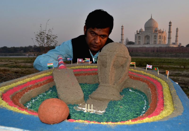 Renowned sand artist Sudarshan Pattanaik with his creation depicting the ICC World Cup near the Taj Mahal in Agra, on Feb 12, 2015.