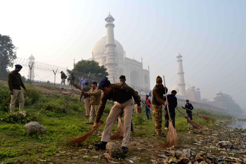 Security personnel participate in Clean India Campaign near the Taj Mahal in Agra, on Dec 25, 2014.