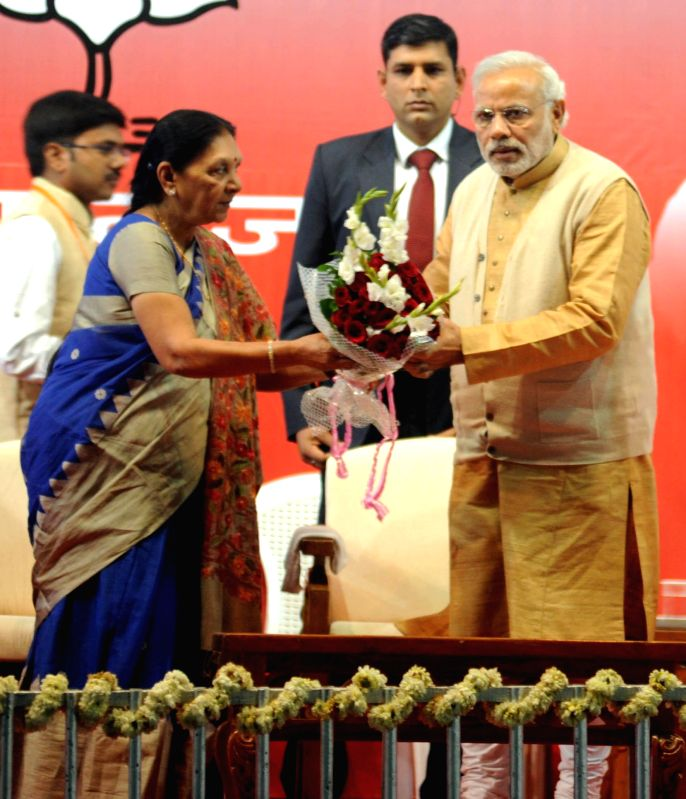 Ahmedabad : Prime Minister Narendra Modi being welcomed by Gujarat Chief Minister Anandiben Patel on his arrival in Ahmedabad on Jan 7, 2015. - Narendra Modi and Anandiben Patel