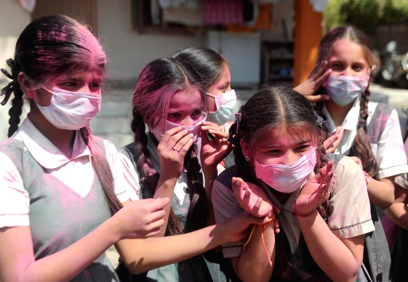 School students celebrate Holi wearing masks as a preventive measure against swine flu in Ahmedabad, on March 5, 2015.