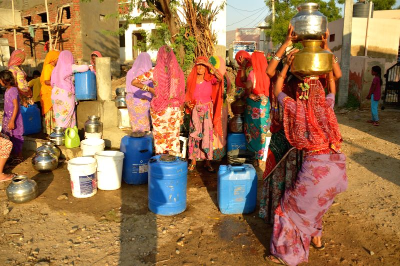 Women fill-up their water vessels in Lohagal village that is facing water shortage in Rajasthan's Ajmer district.
