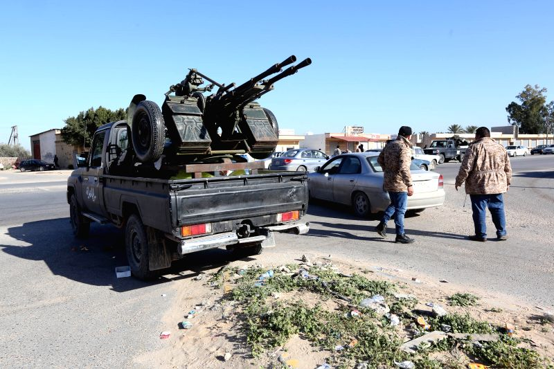 Libya Dawn fighters check passing cars near a local checkpoint in the al-Tusha area, west of al-Azizia, Libya, on April 3, 2015. Clashes continued in al-Azizia on ...