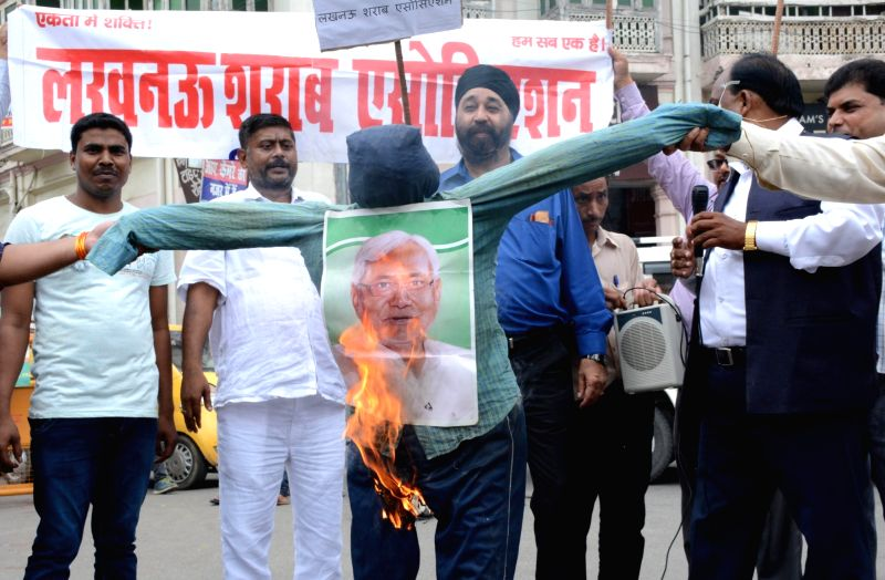 Alcohol vendors and businessmen burn an effigy of Bihar Chief Minister Nitish Kumar in Lucknow, on July 26, 2016. - Nitish Kumar