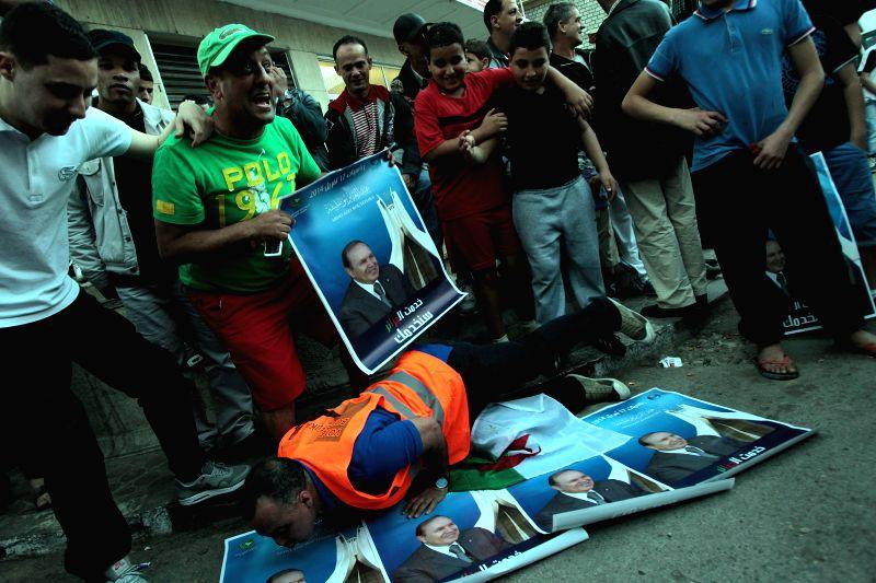 Algerians celebrate Algerian President Abdelaziz Bouteflika's winning of his fourth term in Algiers, capital of Algeria, April 18, 2014. Algeria's incumbent ... - Tayeb Belaiz